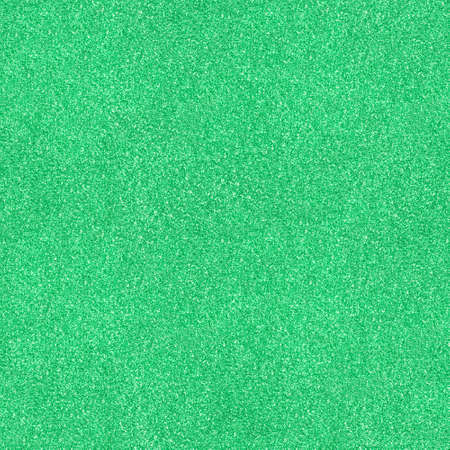Surface texture with green sparkles. Seamless festive background. Light backdrop