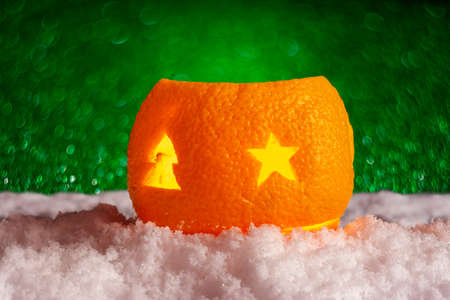 Christmas orange candlestick in the snow. Magical new year background with green bokeh. Foto de archivo