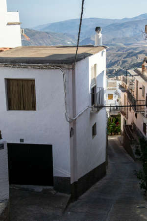 typical sloping streets and houses of the Alpujarra with mountains in the backgroun