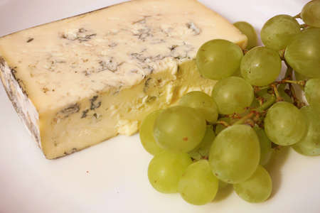 stilton: Red grapes with cheese  on white background.