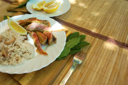 Fried rice  and small fish in plate on table. Bay leaves and lemon. Outdoors Food.    Stock Photo