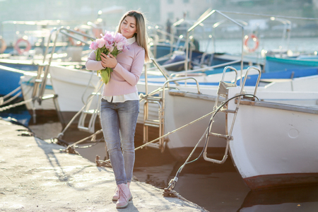 Beautiful girl in spring or autumn, by the sea in the boat Bay. With a bouquet of flowers in his hands and tight stylish jeans and a pink sweater.