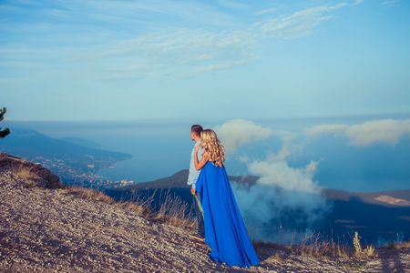 Beautiful couple of newlywed hugging at wedding day on cliff with ocean view. Stylish bride and elegant groom look at each other with love. Concept honeymoon, family, marriage, just married Foto de archivo