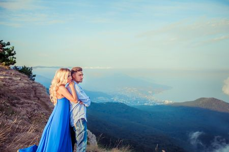 Beautiful couple of newlywed hugging at wedding day on cliff with ocean view. Stylish bride and elegant groom look at each other with love. Concept honeymoon, family, marriage, just married