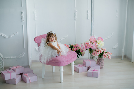 young beautiful girl ballerina in a white pink dress is standing in a white room near a white table holding a bouquet of flowers