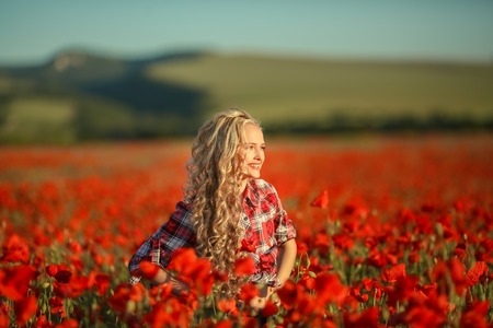 Portrait of a girl on the street with a wreath of poppy flowers on the head. Stock fotó