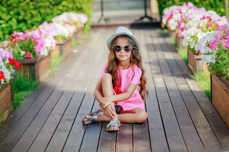 Fashion girl wearing a pink checkered shirt, hat and sunglasses in city. Banque d'images