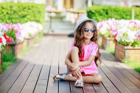 Fashion girl wearing a pink checkered shirt, hat and sunglasses in city. Stockfoto