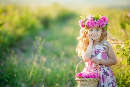 A little girl with beautiful long blond hair, dressed in a light dress and a wreath of real flowers on her head, in the garden of a tea rose.