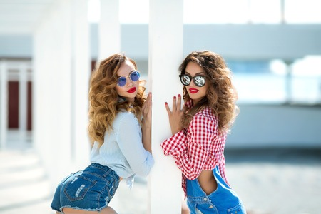 Two attractive girls, cheerful best friends having fun at beach party. Wearing summer outfit, shorts and t-shirts,having fun fashionable looking with beautiful wavy hair. Isolated.hat and sunglasses.