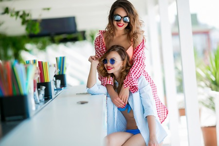 Two attractive girls resting on the beach bar, drink a refreshing cocktail, laughing and having fun. The bright bathing suits and sunglasses