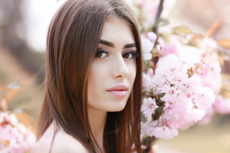 The beautiful girl with a romantic hairstyle and a professional make-up enjoys a smell of pink colors in a garden. The girl dreams. A portrait of the beautiful girl model in the spring in the park