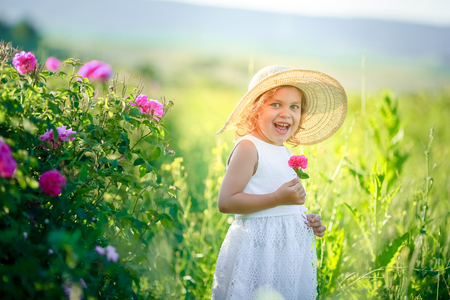 A little girl wearing flower yellow dress with white hat and stand in the yellow flower field of Sunn Hemp Crotalaria Juncea. Stock Photo