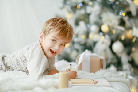 Beautiful little baby boy in pajamas with stars celebrates Christmas. New Years holidays. Toddler play in white Christmas sleigh in the festively decorated room, copy space on right area. Reklamní fotografie