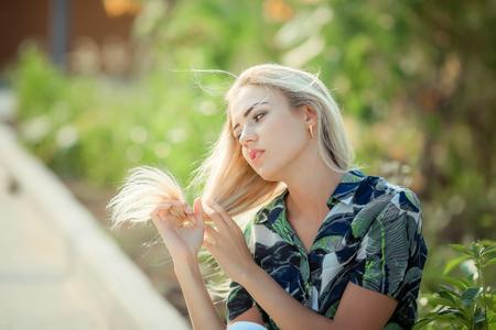 Portrait of beautiful woman with strait hair. Walking in sunflower field Standard-Bild