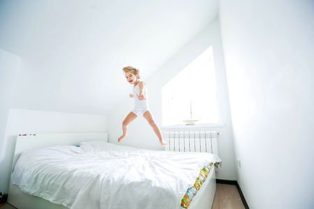 Happy boy playing in white bedroom. Little boy brother play on the bed wearing pajamas. Family at home jumping on the bed and lying 版權商用圖片