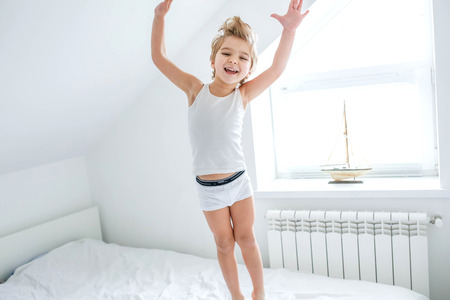 Happy boy playing in white bedroom. Little boy brother play on the bed wearing pajamas. Family at home jumping on the bed and lying