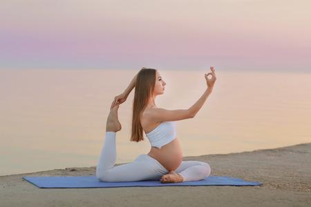 Junge schwangere Frau im weißen Kleid, die am Strand nahe blauem Meer sitzt und atmet. Sommerurlaub während der Schwangerschaft, glückliches Mutterschaftskonzept, nah an den Händen. Standard-Bild