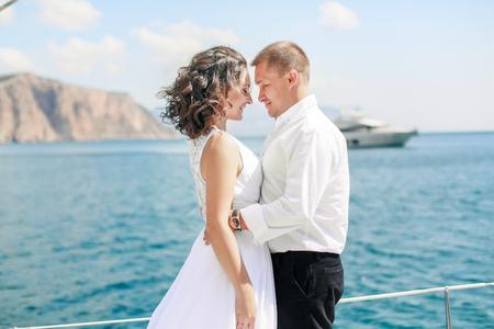 Una coppia appena sposata su yacht. Sposa e sposo felici il giorno del loro matrimonio. Archivio Fotografico