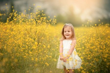 Bambina sorridente sveglia con ghirlanda di fiori sul prato della fattoria. Ritratto di bambino adorabile all'aperto. Mezza estate. Giorno della Terra.