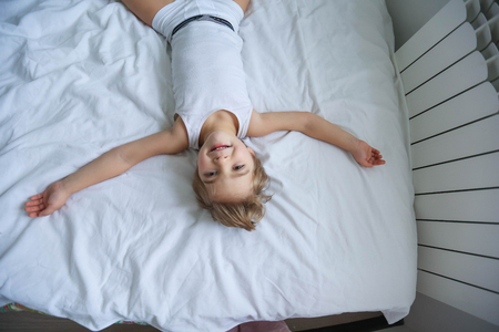 Happy boy playing in white bedroom. Little boy brother play on the bed wearing pajamas. Family at home jumping on the bed and lying Banque d'images