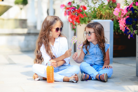A Two cute little sisters eating huge lollipops outdoors on beautiful summer day