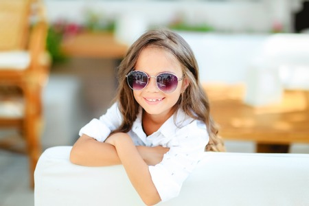 A little girl in fashionable glasses on the terrace background with long curly hair smiles in front of the camera. Summer, fun, family and vacations concept. Two fashion posing.