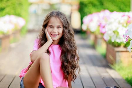 Una niña feliz en el parque en un día de verano. Foto de archivo
