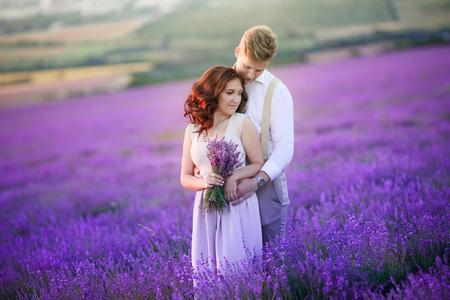 Ein liebevolles Paar, das auf einem Lavendelfeld steht und sich umarmt. Schöne Braut im luxuriösen Hochzeitskleid gekleidet. Braut und Bräutigam sind verheiratet