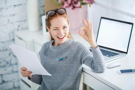 Mujer hermosa joven con el pelo rojo, con gafas, trabajando en la oficina, utiliza una computadora portátil y un teléfono móvil. Foto de archivo