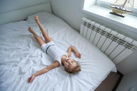 Ragazzo felice che gioca nella camera da letto bianca. Il fratellino gioca sul letto con indosso il pigiama. Famiglia a casa che salta sul letto e si sdraia