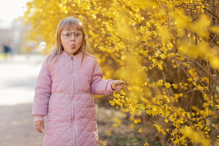 Stylish child girl 5-6 year old wearing trendy pink coat in autumn park. Looking at camera. Autumn season. Childhood. Shes posing as a model