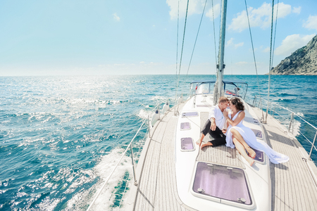 Young Couple Relaxing on a Yacht. Happy wealthy man and a woman by private boat have sea trip Stockfoto