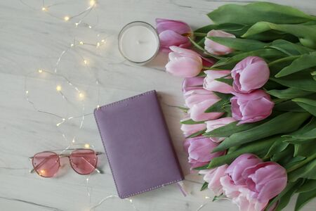 Glasses, tulips and accessories in pink color on white wooden table