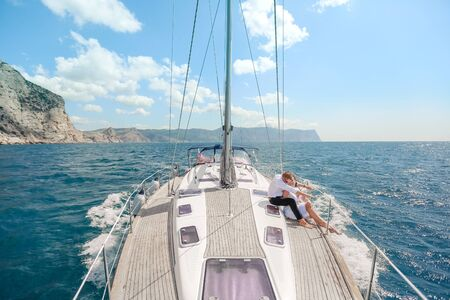 white yacht with sail set goes along the island on a hot day. blue sea, blue sky. Crimea. on board a young couple in love. the bride and groom. wedding boat trip.