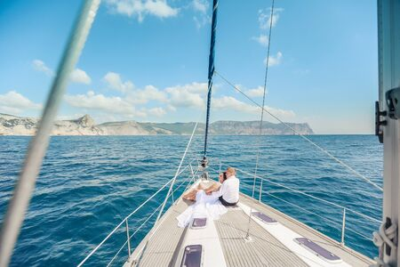 Young Couple Relaxing on a Yacht. Happy wealthy man and a woman by private boat have sea trip Banco de Imagens