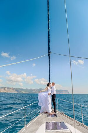 Young Couple Relaxing on a Yacht. Happy wealthy man and a woman by private boat have sea trip Stock Photo