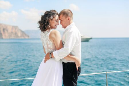 Just married couple on yacht. Happy bride and groom on their wedding day,
