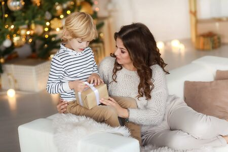 Mom gives the child a New Years gift and hugs him.