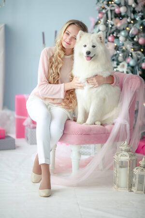 A curly-haired blonde with a best and faithful friend a purebred dog poses in a New Years decorated studio. Zdjęcie Seryjne