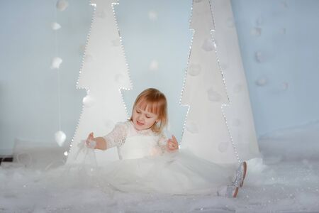 Cute girl in white Princess costume between white artificial glowing Christmas trees.