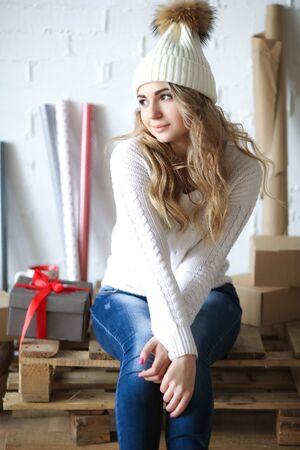 Beautiful girl in cap master making packaging for gifts. Stock fotó