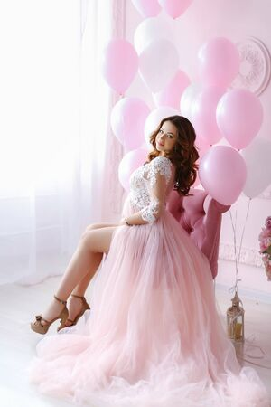 Elegant woman in a bride dress on a background of pink inflatable balloons.
