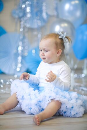 Cheerful childrens birthday baby girl on a background of blue air-blasting and blue papyrus circles.