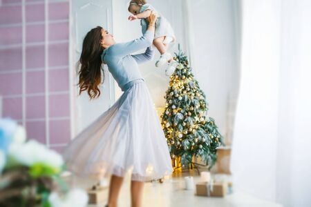 Family of two people mother and daughter 1 year old against the background of the Christmas tree photo in bright colors.