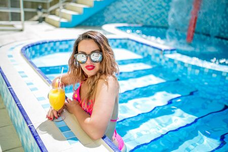 Young sexy woman in swimming pool and drinking cocktail.