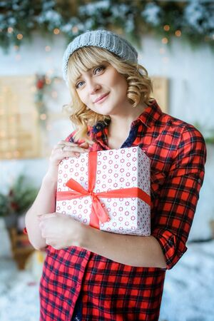 A woman in a red Christmas shirt and a hat on her head holds a Christmas gift.
