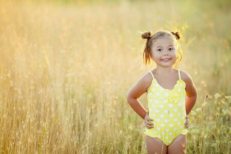 Little girl 3-5 years old in the summer in the field with yellow spikelets in a yellow swimsuit.