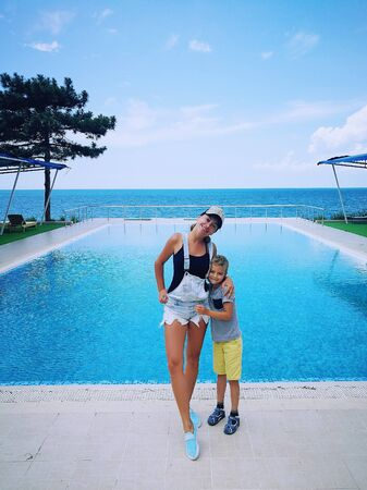 Mother and son on the background of a rectangular pool near the sea.