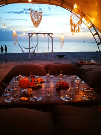 Views of the sea and the laid table with view of the sea during sunset.